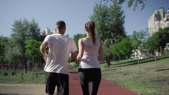 Thumbnail for Back View of Adult Couple of Joggers Running Along Track on Summer Morning. Camera Follows Fit