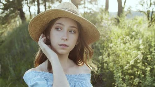 Smiling Girl Teenager in Straw Hat Looking to Camera on Summer Wood Landscape