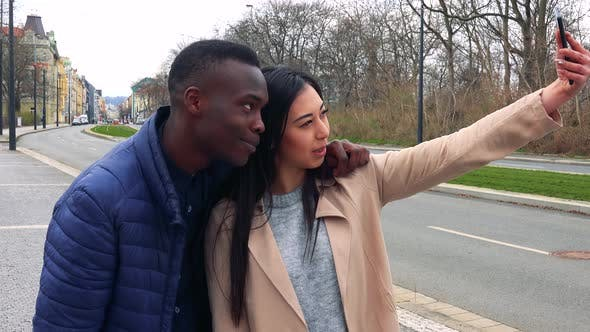 Thumbnail for A Black Man and a Young Asian Woman Take a Selfie with a Smartphone in a Street in an Urban Area