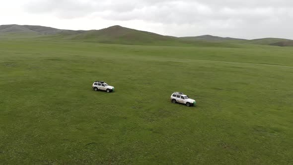 Two 4X4 Suv Cars Driving in The Treeless Vast Meadow