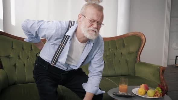 Grandfather in Glasses and with Beard Is Having Pain in Back Grabs Lower Back with His Hands While