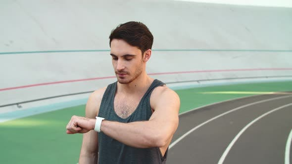 Thumbnail for Portrait of Sport Man Using Smart Watch on Track. Man Runner Checking Results