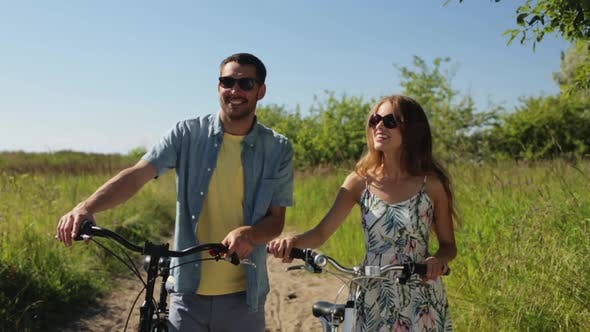 Thumbnail for Happy Young Couple with Bicycles Walking in Summer