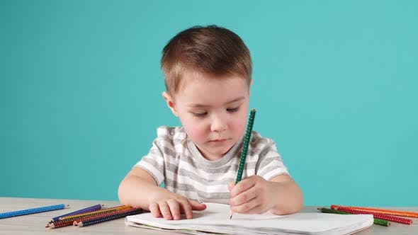 Happy Child Drawing with Pencils in Album, Isolated on Blue