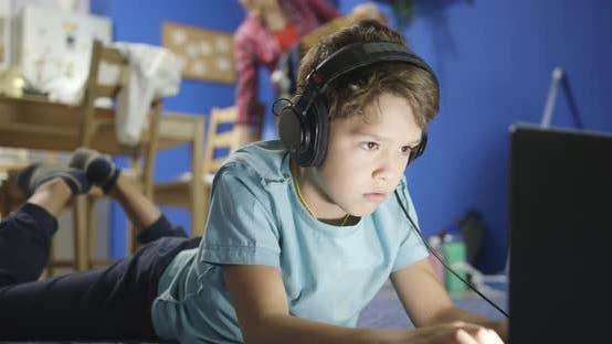 Porträt von Little Boy Musik vom Notebook durch Kopfhörer beim Liegen auf Hartholz