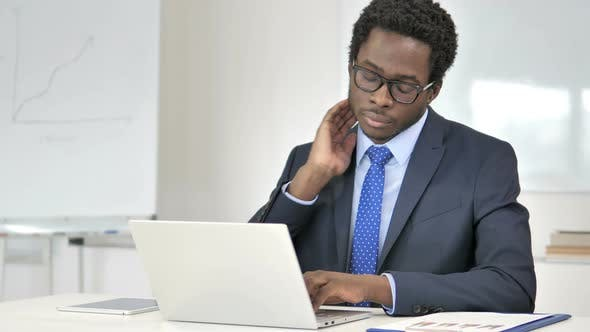 Thumbnail for African Businessman with Neck Pain Working on Laptop