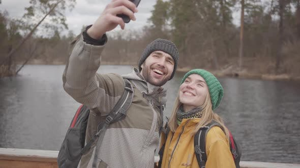 Thumbnail for Portrait of Young Couple of Travelers Taking Selfie While Standing on a Bridge