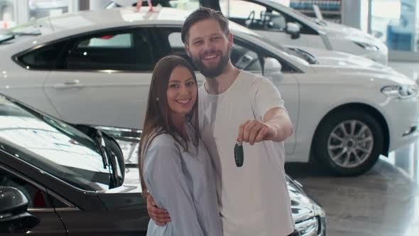 Thumbnail for The Concept of Buying or Renting a Car. Young Happy Interracial Couple with New Car Keys