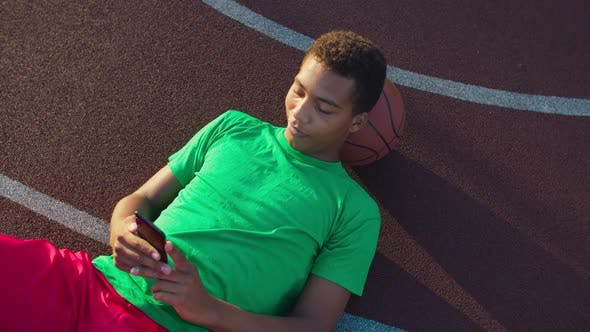 Thumbnail for Basketball Player with Cellphone Resting on Court