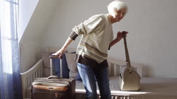 Thumbnail for Beautiful 70-Something Lady with Suitcase Departing from Hotel Room