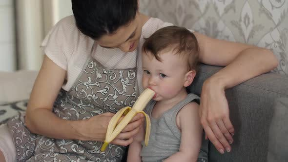 Baby Eats Banana with Mother's Help