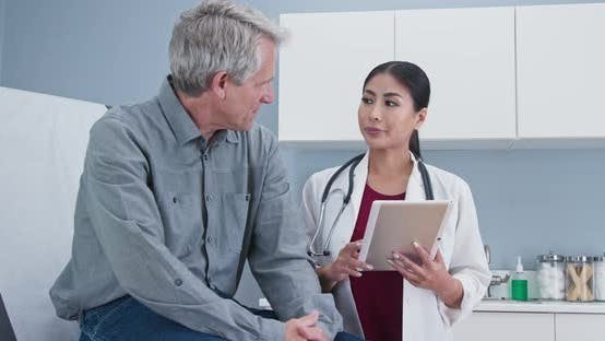 Thumbnail for Asian woman doctor talking senior Caucasian male patient sitting on exam table