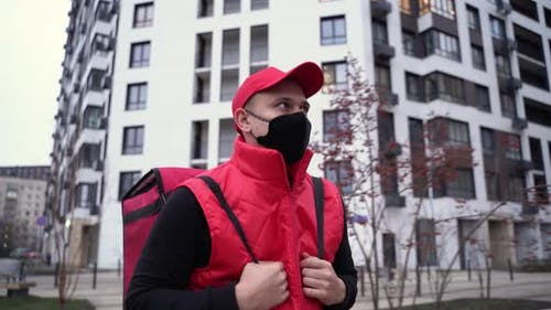 Delivery Guy Wearing Red Uniform and Black Mask While Walking Along Modern Buildings Down City