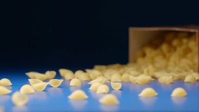 Falling a box with a pasta (conchiglie) - From a side