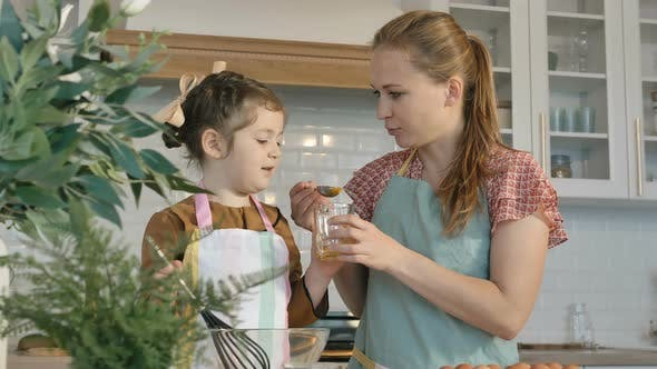 Thumbnail for Woman Feeds Little Girl with Raw Yolk Making Pie in Kitchen