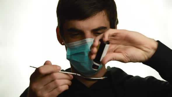 Thumbnail for Portrait of a Young Man in a Medical Mask Makes Dripping Drops of Medicine Into a Spoon Removes the