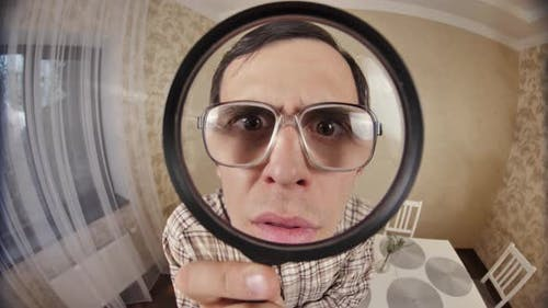 Funny Man Looks Through Magnifier Glass