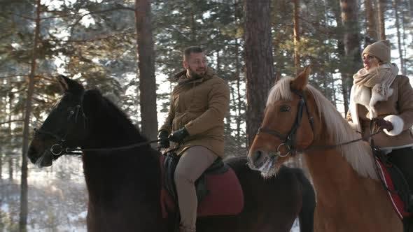 Thumbnail for Couple Enjoying Horseback Riding Date on Winter Day