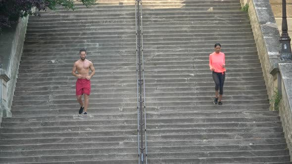 Thumbnail for A couple running on stairs in a city as a workout.