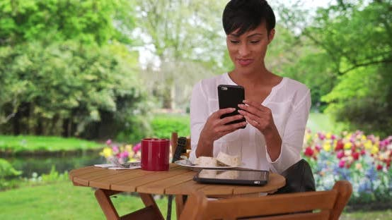 Thumbnail for Mixed race female enjoying breakfast in garden facetimes friend via smartphone