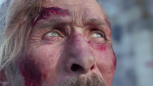 Old Wounded Cossack with Mustache Thinks and Looks at Camera with Sad Eyes