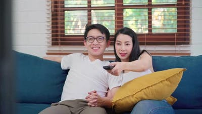 Asian couple watching television in living room at home, sweet couple enjoy love moment.