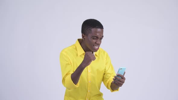 Thumbnail for Young Happy African Businessman Using Phone and Getting Good News