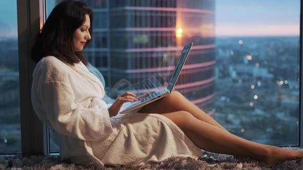 Thumbnail for Young Woman in a Bathrobe Is Sitting Near a Window on a High Floor in a Hotel. Girl Resting