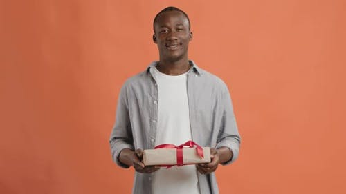 Cheerful Black Guy Offering Exclusive Gift Box To Camera