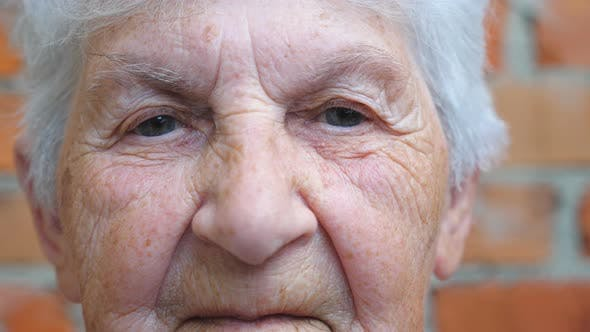 Portrait of Elderly Woman with Gray Hair Looking Into Camera. Detail View on Wrinkled Female Face
