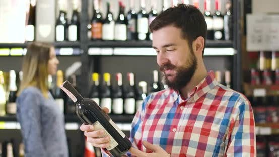 Thumbnail for Portrait of Young Smiling Caucasian Man Reading Label on Wine Bottle, Looking at Camera and Showing