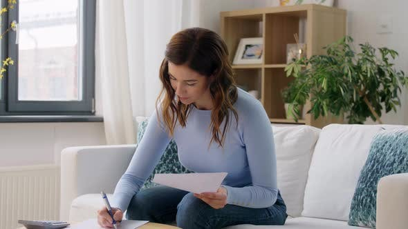 Woman with Papers and Calculator at Home