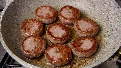 Beef patties in the frying pan close up