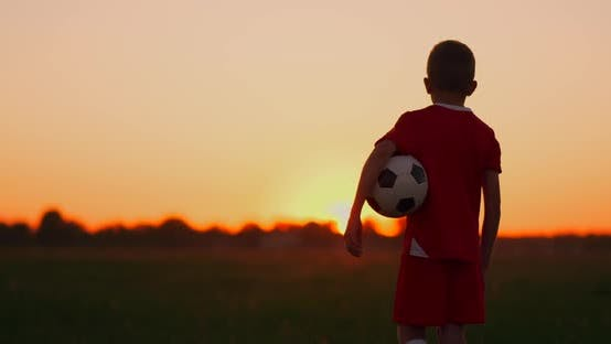 Cover Image for Boy Football Player with the Ball Is on the Field the Setting Sun the Camera Follows the Boy