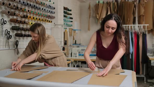 Two seamstresses working with a cloth and a chalk on a table. Female dressmaker uses chalk