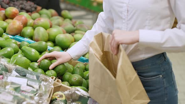Young Woman in the Organic Store Buying Vegetables and Fruits the Female Collects Avocado Fruits in