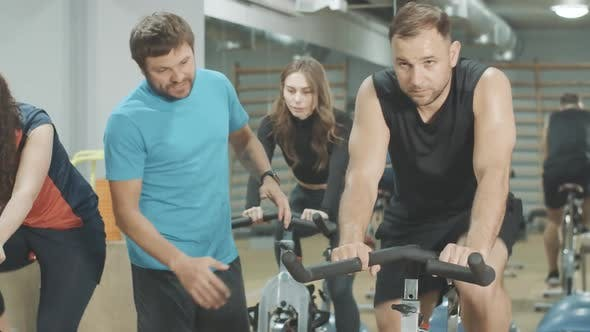 Thumbnail for Trainer in Blue T-shirt Endorsing Young Handsome Sportsman Cycling in Gym. Professional Employee