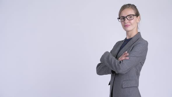 Thumbnail for Profile View of Young Happy Businesswoman Looking at Camera with Arms Crossed