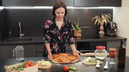 Young cheerful woman puts tasty baked pizza on wooden table. Process of making pizza