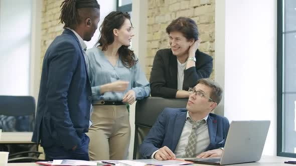 Multiethnic Colleagues Discussing Project with Young Man Sitting at the Table with Laptop