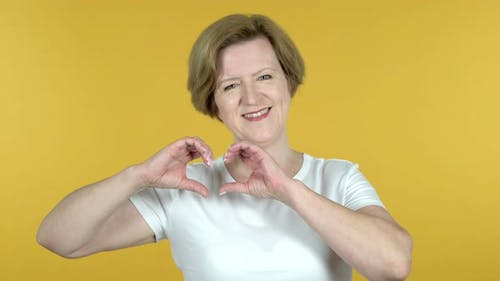 Handmade Heart By Old Woman Isolated on Yellow Background