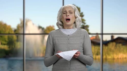 Mature Woman Sneezing or Blowing Nose.