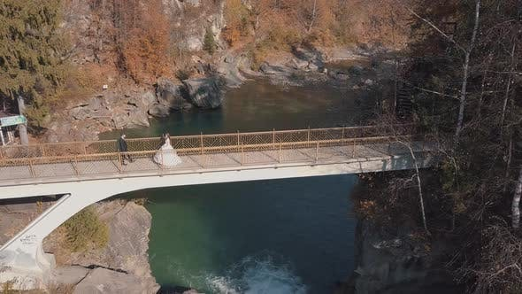 Thumbnail for Newlyweds. Bride and Groom on a Bridge Over a Mountain River. Aerial View