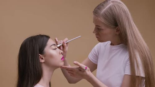 Professional Make Up Artist Making Ceremonial Makeup for Beautiful Asian Lady