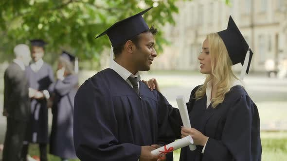 Thumbnail for Graduates in academic regalia talking, girl fixing tie, guy kissing her on cheek