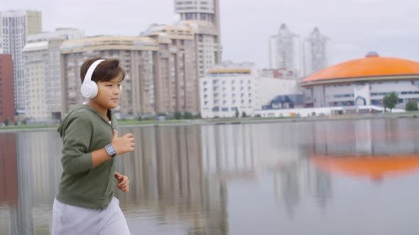 Thumbnail for Young Asian Boy in Headphones Jogging along City Riverside