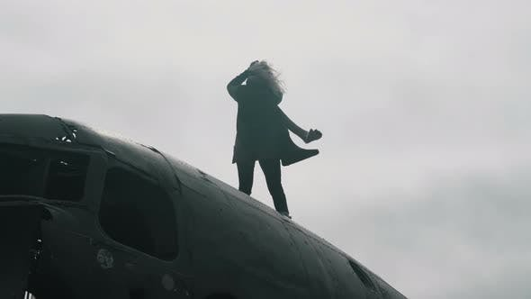 Thumbnail for Young Blonde Woman Standing on Top of Crashed DC3 Plane in Iceland and Looking Around, Hair Wave on