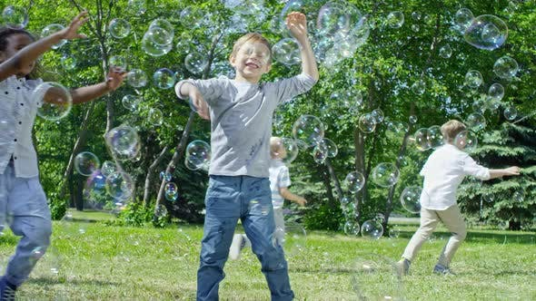 Thumbnail for Kids Chasing Bubbles on Green Lawn in Park