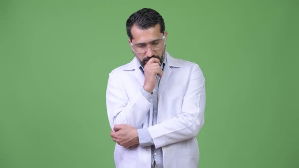 Serious Persian Bearded Man Doctor Wearing Protective Glasses While Thinking