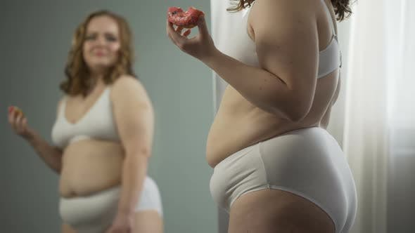 Thumbnail for Overweight Young Woman Stress Eating in Front of Mirror, Hating Her Fat Body